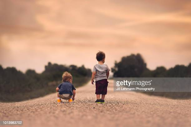 2 year old fraternal twin boys stand on a gravel road in the iowa summer - 2 3 anos - fotografias e filmes do acervo
