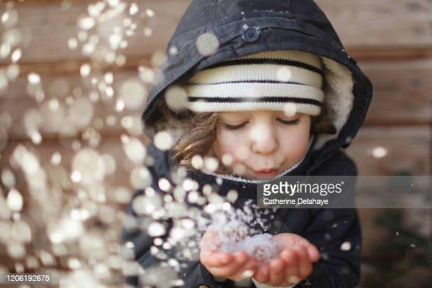a 4 year old girl blowing on snowflakes - holiday stock pictures, royalty-free photos & images