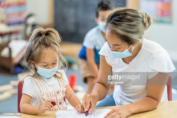3 year old girl colouring at daycare wearing a mask - servizi per l'infanzia foto e immagini stock