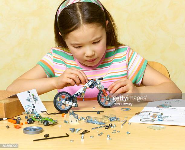 8 Year old girl constructing model of motorcycle.