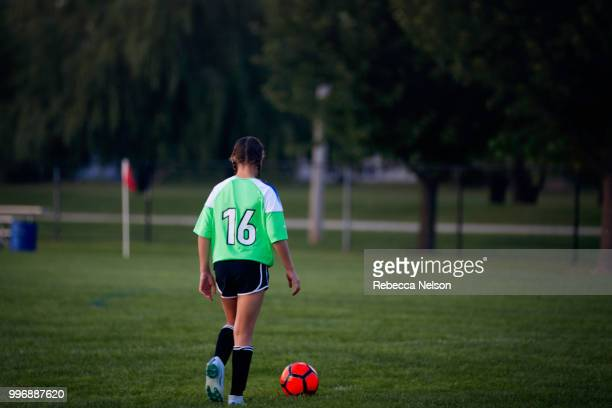 11 year old girl dribbling soccer ball on field, rear view - ligue professionnelle nord américaine de football photos et images de collection