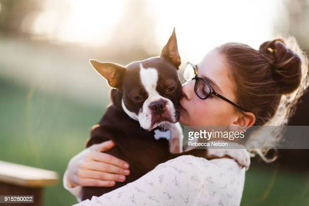 10 year old girl holding her Boston Terrier dog