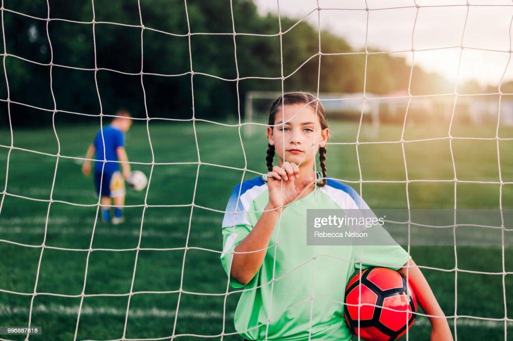11 year old girl holding soccer ball looking through soccer goal net : Foto de stock