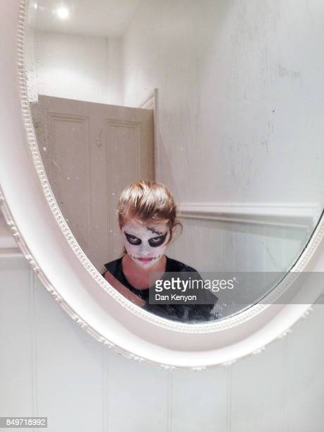 11 year old girl in halloween makeup looking in bathroom mirror