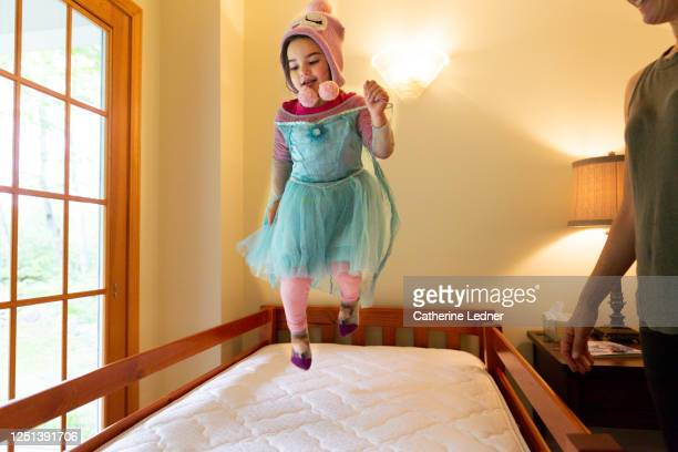 3 year old girl in her favorite costume jumping on made be with mom standing by - catherine ledner stock pictures, royalty-free photos & images