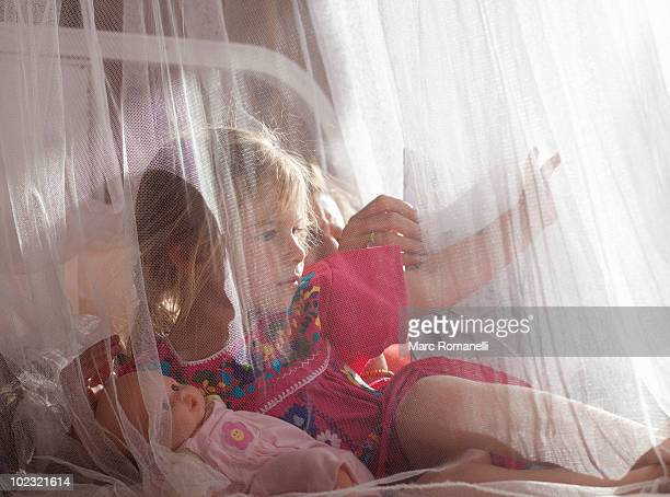 4 year old girl in outdoor bed - mosquito net stock photos and pictures