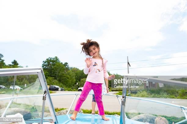 3 year old girl in pink dancing on top of a vintage motorboat - catherine ledner stock pictures, royalty-free photos & images