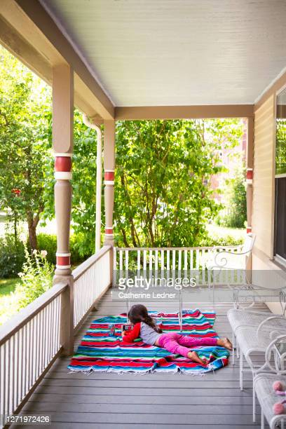3 year old girl lying on belly looking at phone on side porch of victorian house. - catherine ledner stock pictures, royalty-free photos & images
