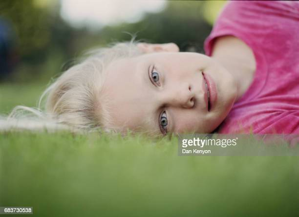 10 year old girl lying on lawn. portrait close up. low angle