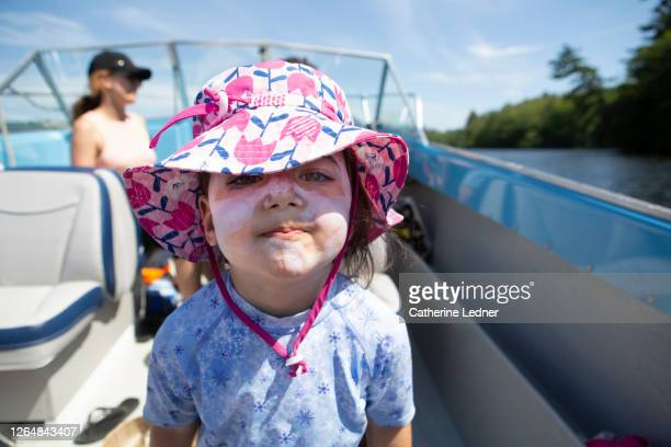 3 year old girl making a face to camera while on a motorboat ride with her parents in maine. - catherine ledner stock pictures, royalty-free photos & images