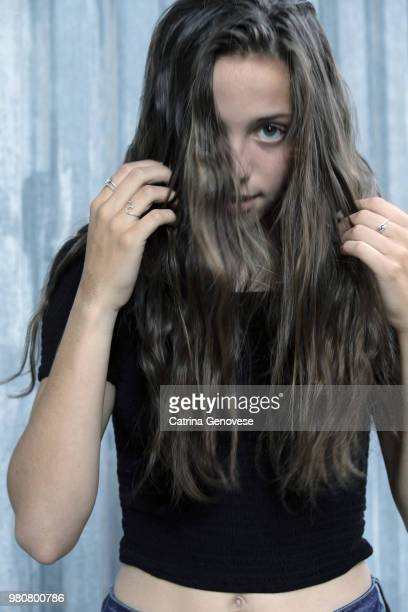 16 year old girl outdoors  covering her face with her long hair