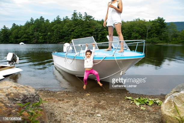 3 year old girl playing and hanging off the side of beached motorboat with mother standing on boat deck - catherine ledner stock pictures, royalty-free photos & images
