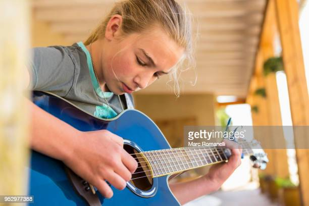12 year old girl playing guitar - 12 13 jaar stockfoto's en -beelden
