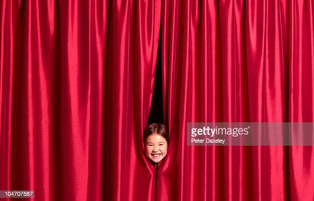 9 year old girl putting face through curtains - theatrical performance stock pictures, royalty-free photos & images