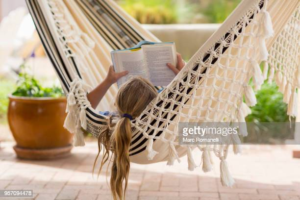 12 year old girl reading book in hammock - 12 13 jaar stockfoto's en -beelden