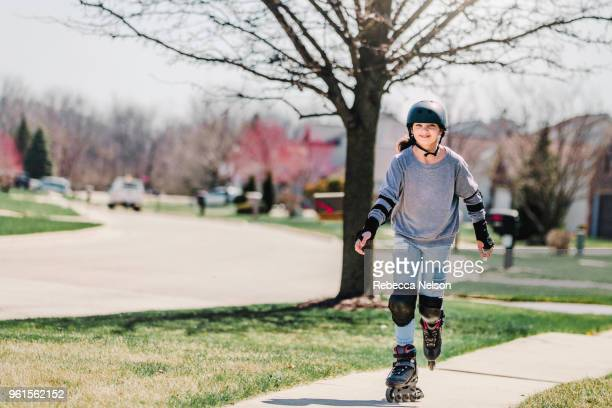 11 year old girl rollerblading in helmet, knee pads and elbow pads - padding stock photos and pictures