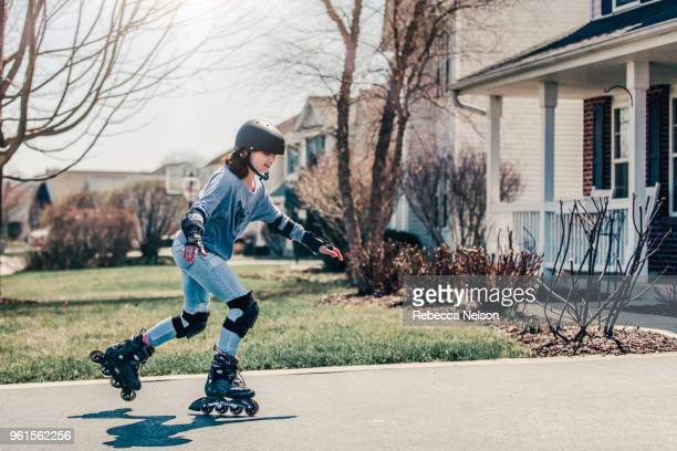 11 year old girl rollerblading in helmet, knee pads and elbow pads