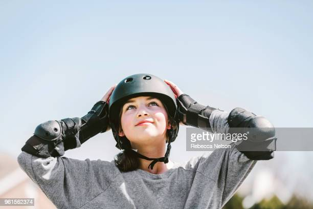 11 year old girl rollerblading in helmet, knee pads and elbow pads - sportschutzhelm stock-fotos und bilder