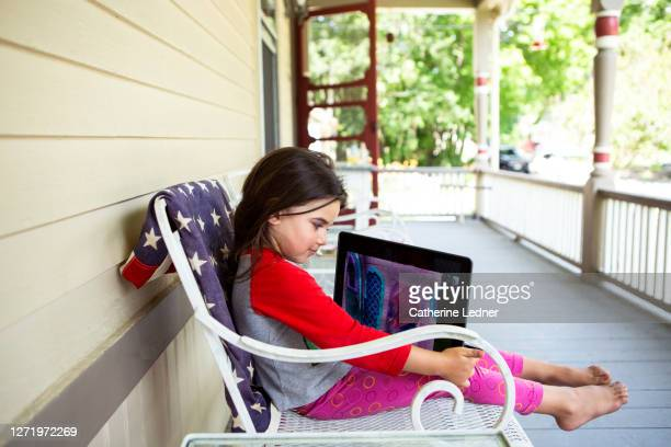 3 year old girl sitting on iron patio chair on victorian porch holding and looking at a digital tablet - catherine ledner stock pictures, royalty-free photos & images