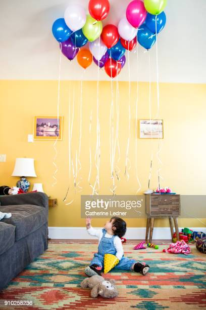 1 year old girl sitting on rug reaching at helium balloons above her