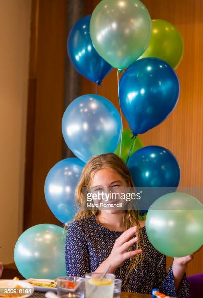 12 year old girl smiling with holding balloons
