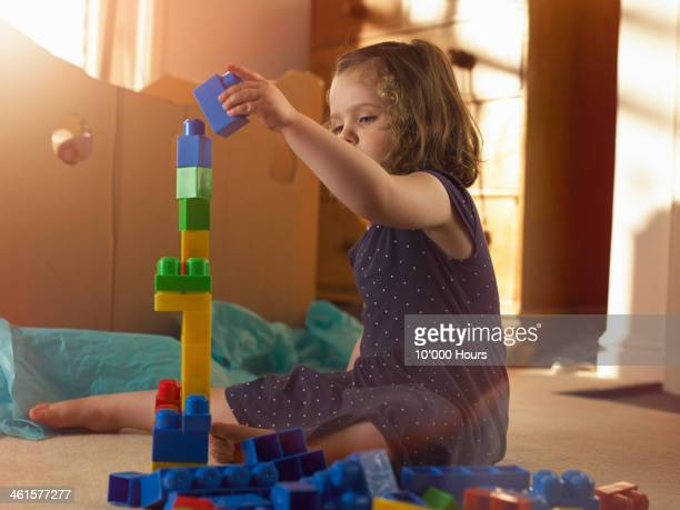 3 year old girl stacking blocks in bedroom