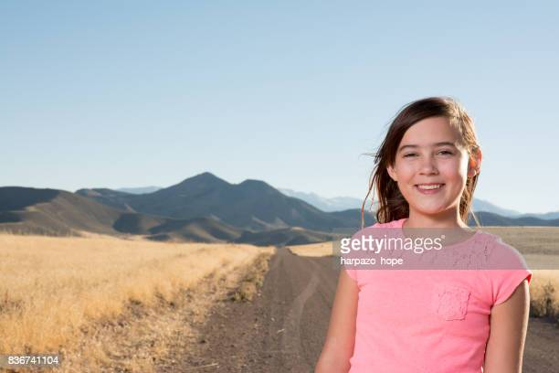 12 year old girl standing on a dirt road.