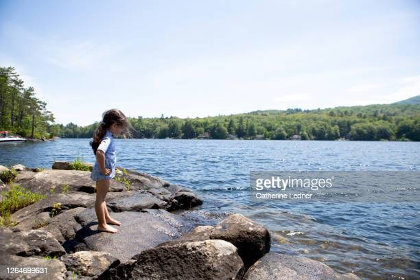 3 year old girl standing on granite rocks at the edge of a lake in maine - catherine ledner stock pictures, royalty-free photos & images