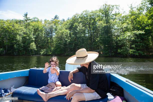 3 year old girl swiping iphone while seated in a motorboat with adult in large sunhat seated next to her. - catherine ledner stock pictures, royalty-free photos & images