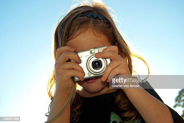 5 year old girl taking a photograph