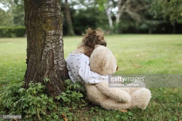 a 5 year old girl talking with her big teddy bear in the garden - treuren stockfoto's en -beelden