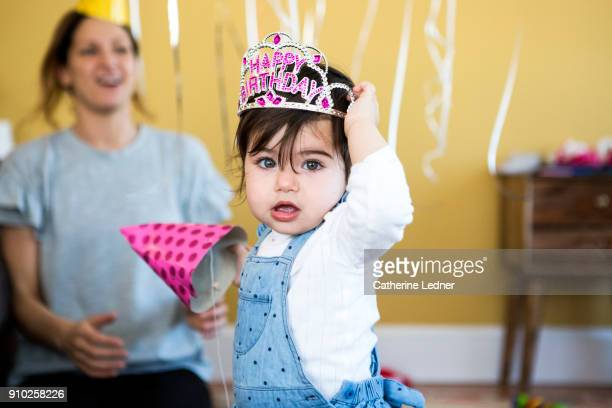 1 year old girl tugging at happy birthday crown on her head - happybirthdaycrown stock pictures, royalty-free photos & images