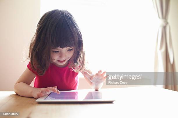 4 year old girl using digital tablet on table