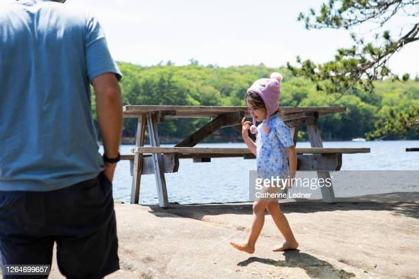 3 year old girl walking at lakes edge with winter hat on and father standing nearby - catherine ledner stock pictures, royalty-free photos & images