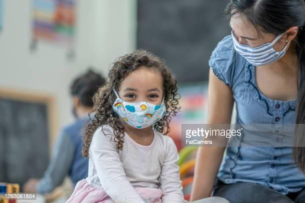menina de 4 anos usando uma máscara facial protetora na creche - criança de escola fundamental - fotografias e filmes do acervo