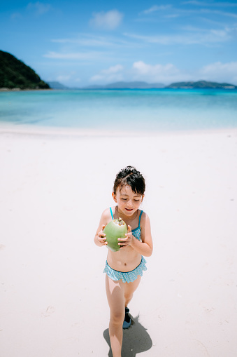 5 year old girl with coconut on tropical beach, Okinawa, Japan - gettyimageskorea