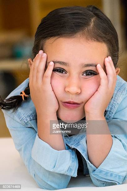 8-10 Year Old Girl With Face in Hands Looking at Camera
