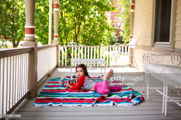 3 year old girl with make up and phone relaxing with mexican blanket on victorian porch - catherine ledner stock pictures, royalty-free photos & images