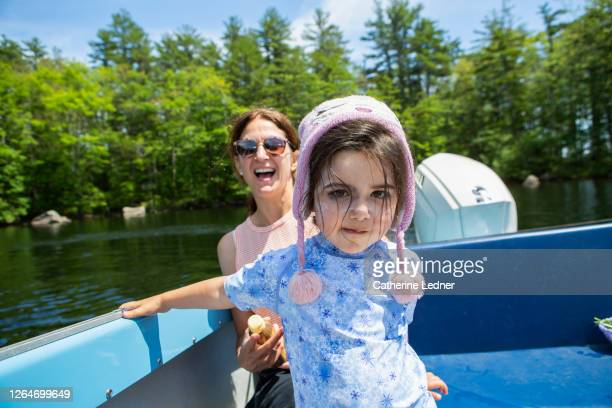 3 year old girl with winter hat on in a motor boat during the summer. - catherine ledner stock pictures, royalty-free photos & images