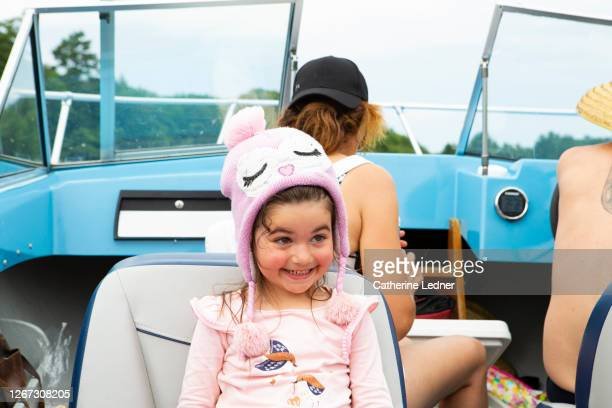 3 year old girl with winter hat on in summer making a super smiley funny face on vintage motorboat with parents up front. - catherine ledner stock pictures, royalty-free photos & images