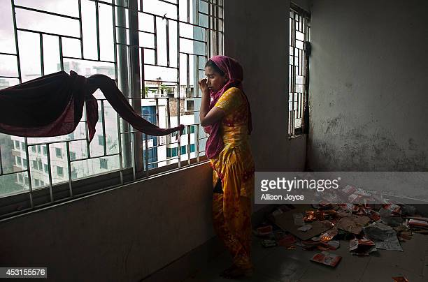 30 year old Halima looks out the window while on a hunger strike at a Tuba Group factory August 4 2014 in Dhaka Bangladesh Garment workers have been...