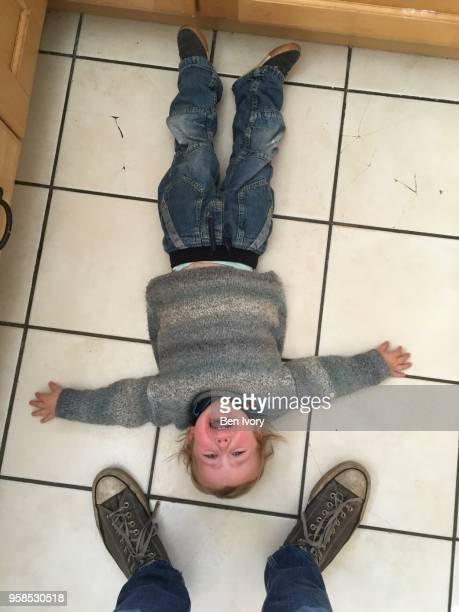 2 year old having a tantrum on the floor, adults feet stood next to him - alleen kinderen stockfoto's en -beelden