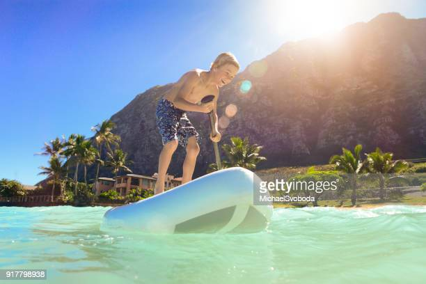 7 year old having fun on a paddle board in hawaii - oahu stock pictures, royalty-free photos & images
