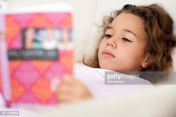7 year old hispanic girl laying down reading a book