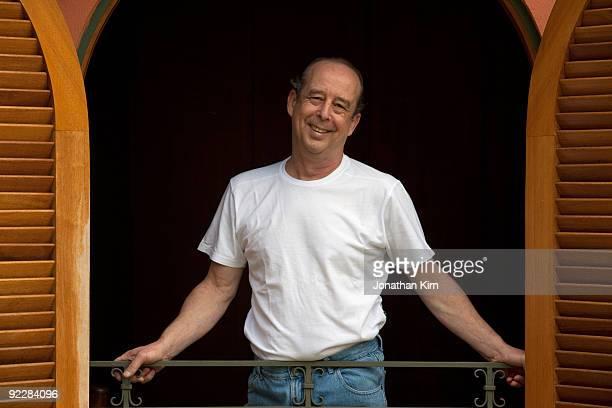 61 year old Hispanic man smiles at window.