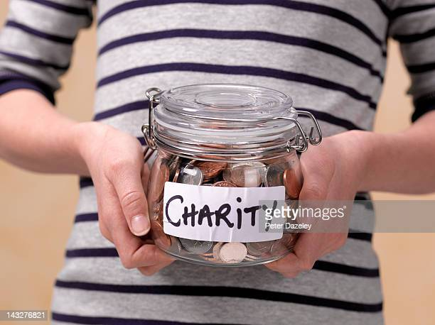 10 year old holding charity donations in a jar - charity and relief work stock pictures, royalty-free photos & images