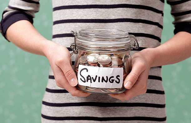 year old holding savings in jar picture