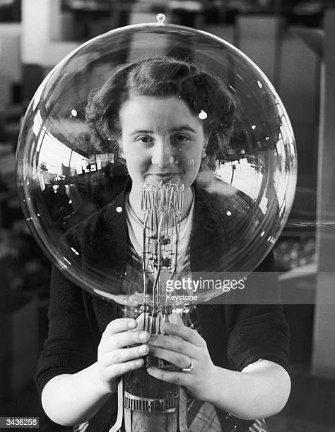 Year old Kathleen Browne helps make enormous bulbs for use in lighthouses around the British coastline at the lamp factory in Wembley, Middlesex.
