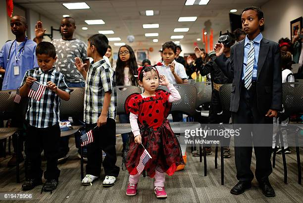 4 year old Kathy Pham dressed as a ladybug says the Pledge of Allegiance while participating in a Halloweenthemed US citizenship ceremony at the US...