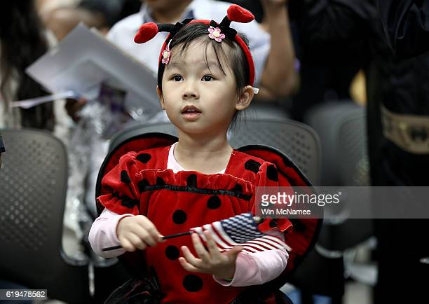 4 year old Kathy Pham dressed as a ladybug takes part in a Halloweenthemed US citizenship ceremony at the US Citizenship and Immigration Services...
